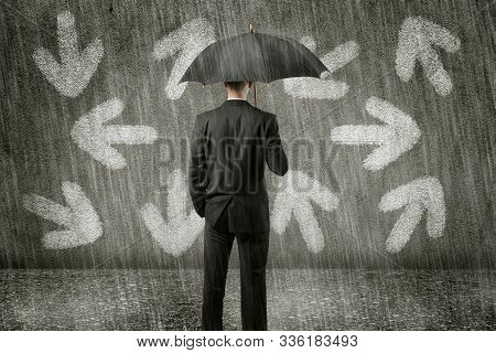 Confused Businessman Standing In Front Of Wall On A Gloomy Day Has To Make A Decision