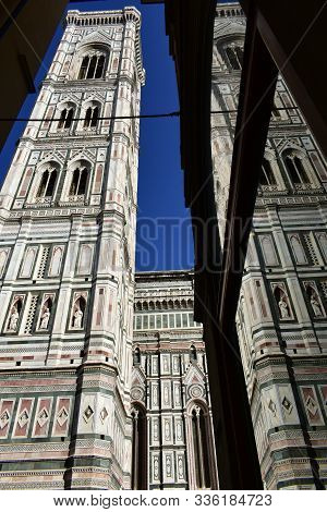 Campanile di Giotto (Santa Maria del Fiore Cathedral bell tower) from nearby street with glass reflection. Florence, Italy.