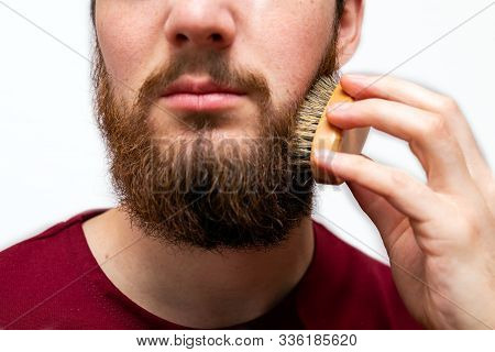 Closeup Of Handsome Man Brushing His Beard On White Background Isolated