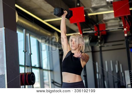Young Blonde Woman Doing Exercises With Dumbbell In Gym: Fit Female Lifting Big Iron Dumbbell Above