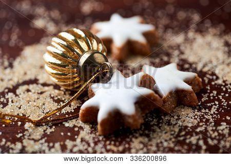 Christmas Golden Bauble, Christmas Cookies (cinnamon Stars) And Brown Sugar On Dark Background. Clos