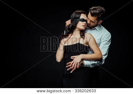 Handsome Bearded Man Looking At Blindfolded Girlfriend Isolated On Black
