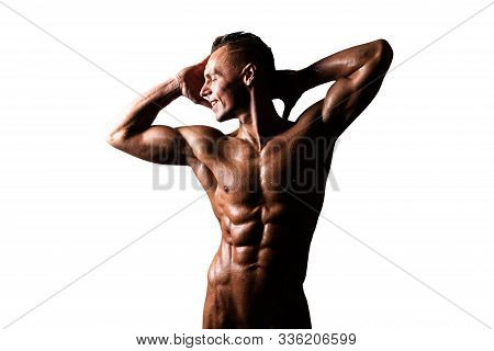 Athletic, Tanned Man With A Naked Torso, Holds His Hands Behind His Head. Isolated On A White Backgr