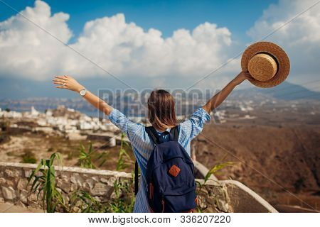 Santorini Traveler With Backpack Raised Arms Feeling Happy Looking At Akrotiri, Mountains Landscape