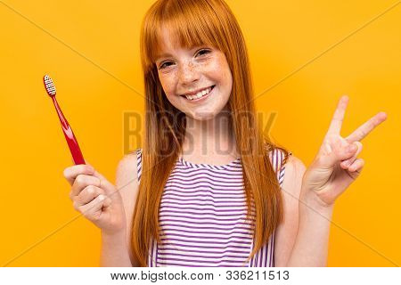 Red-haired Girl Holds A Toothbrush In Hands Over Yellow Background.