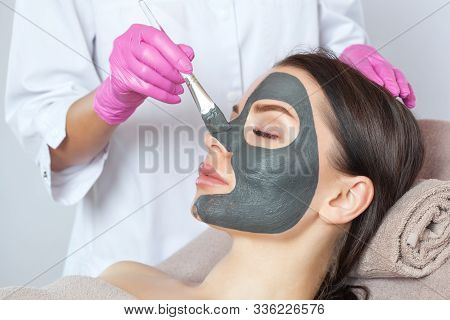 Beautician Makes A Black Clay Mask To Rejuvenate The Skin To Beautiful Woman.cosmetology Concept And