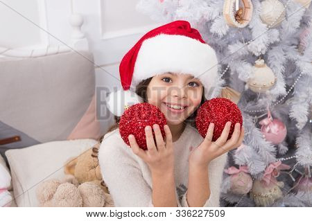 Playful Mood. Creating Festive Atmosphere. Child Decorating Christmas Tree With Red Ball. Girl Kid D