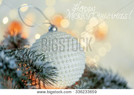 Christmas Holiday Greeting Card. White Ball With Nacre Pearls, Pine Branches And A Garland In The Sn