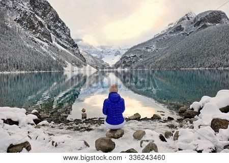 Woman Sitting On Rock Looking At Scenic View Of Calm Lake And Reflections Of Surrounding Mountains W