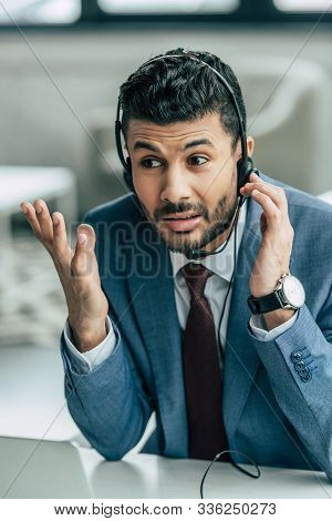 Discouraged Call Center Operator In Headset Showing Indignation Gesture