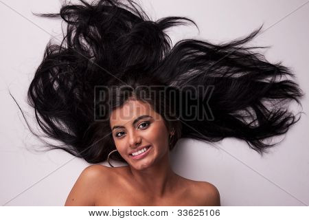Happy And Beautiful Latin Woman, Lying On The Floor, Looking To Camera,  Studio Shot
