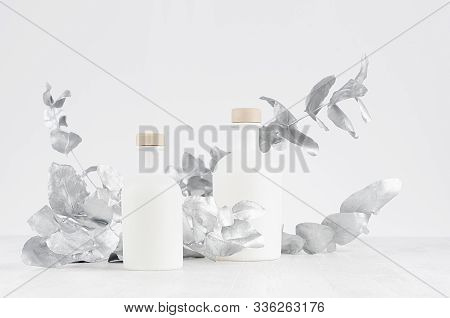 Blank Cosmetic Glass White Bottles With Beige Bungs Decorated Silver Leaves On Light White Wood Tabl