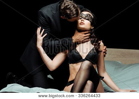 Man Touching Neck Of Sexy Woman In Underwear And Blindfold Isolated On Black