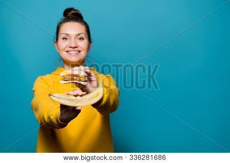 A Girl In A Sweatshirt Shows A Cutaway Banana And A Burger, Selective Focus