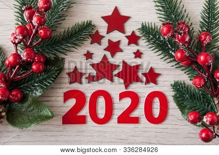New Year's composition. Christmas tree branches with berries on a wooden background.  New year concept. Flat lay. Top view