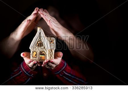 Female Hands Hold A Toy House, And Male Hands Form A Roof Over The House, Close Up