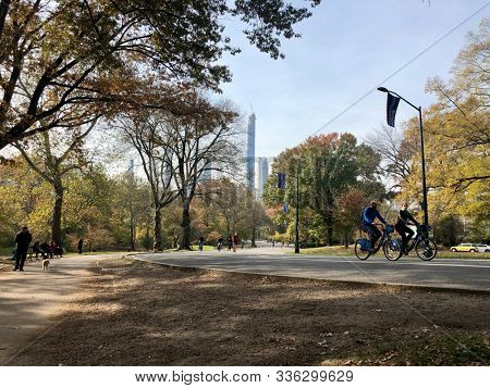 NEW YORK, USA - NOVEMBER 11, 2019: People running, walking and cycling on an Autumn day through Central Park in New York, USA.