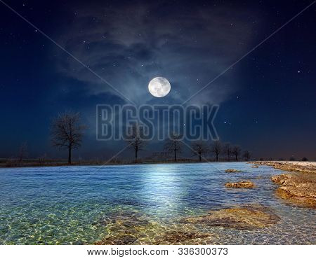 Full Moon And Clear Rocky Lake. Moonlight Night Fantasy.