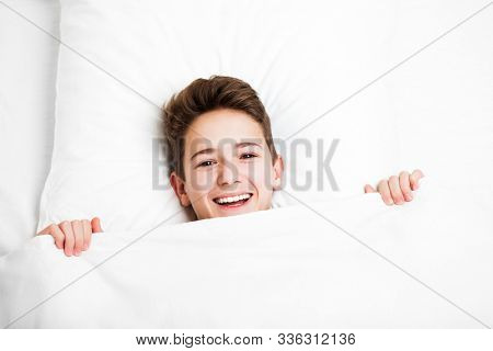 Happy handsome toothy smiling child boy lying bed and resting before morning awake after night sleep