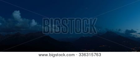 Nocturnal Alpine Landscape With Mountains And Clouds