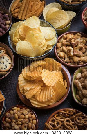 Salty snacks served as party food in ceramic bowls