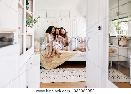 Beautiful Smiling Girls Of Different Ethnicity Hugging And Have Fun Together Inside The Camper Van.