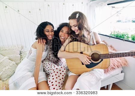 Attractive Happy Women Of Different Ethnics With Guitar Have Fun Together Inside The Camper Van. Wom