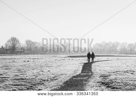 High-contrast Black And White Image Of A Man And A Woman Walking Together On A Meandering Path In A