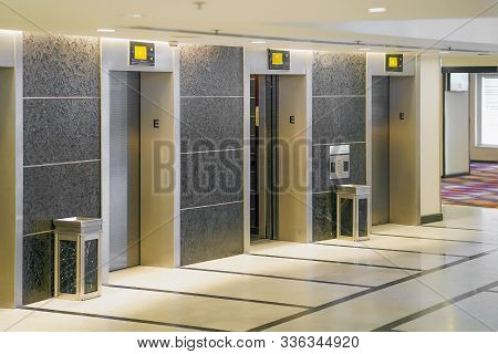 View Of Elevator Doors In Office Building. Wide Angle View Of Several Modern Elevators With Closed D