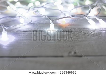 Christmas Tree Lights Or Fairy Lights Over Festive White Wooden Board Background With Copy Space