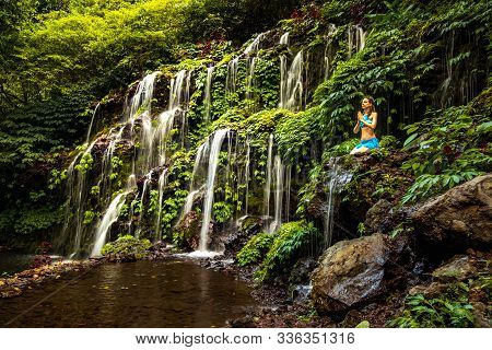 Caucasian Woman Sitting On The Rock, Practicing Yoga And Pranayama Near Waterfall. Hands In Namaste
