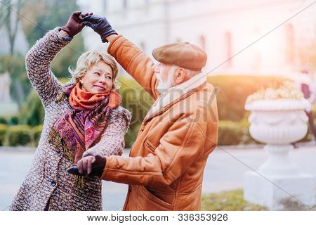 Happy Old Couple Dancing At Autumn Park. Senior Ma Flirting With Blonde Elderly Woman Outdoors In Ci