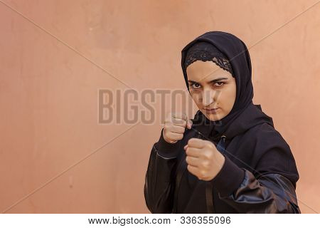 Muslim Boxer Woman In Islamic Sportswear. Muslim Fighter Boxer Posing Doing Exercises. Healthy Lifes