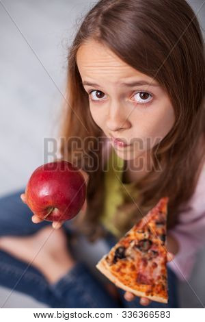 Puzzled young girl undecided wheter to choose the appetizing pizza or healthy apple - holding them in her hands