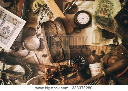 Different Antique Items On The Table: Old Pocket Watches, Banknotes And Coins Of The Russian Empire,