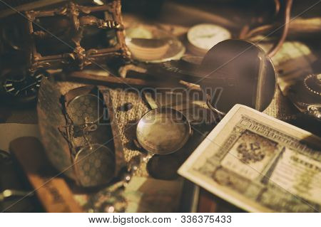 Different Antique Items On The Table: Bronze Jewelry, Banknotes And Coins Of The Russian Empire, Gla