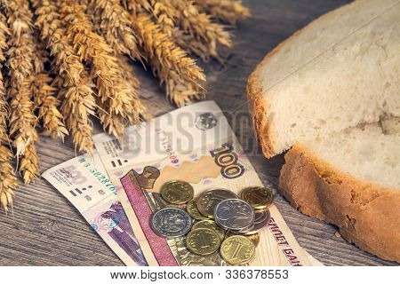 A Loaf Of Bread And Ears Of Ripe Wheat Lie On A Wooden Table Next To Russian Rubles. Bread And Wheat