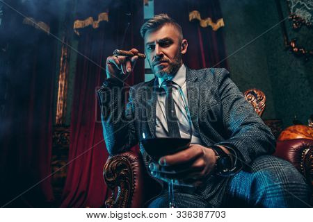 A portrait of a handsome mature man in a formal costume smoking a cigar and drinking wine in the interior. Men's beauty, fashion.