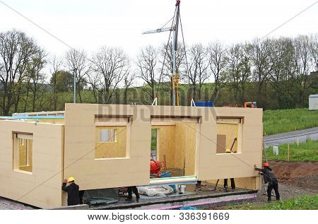 Assembly Of A Prefabricated Timber House, With A Crane In The Background