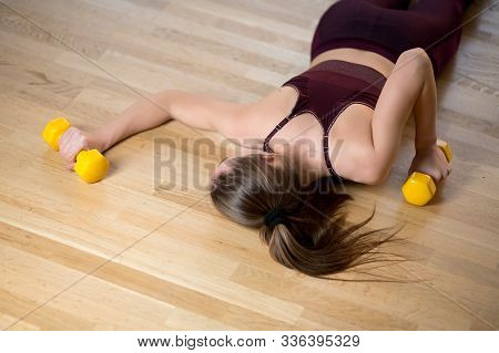 The Athlete Is Exhausted And Lies On The Floor In The Gym With Dumbbells In Her Hands, Top View