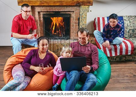 Big Family Are Spending Time Together Near Fireplace: Adults Are Drinking Wine And Looking At The No