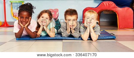 Happy children are lying on a mat during a kid's gymnastics in the gymnasium