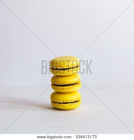Three Yellow French Macarons On A Wooden Table. Banana Macarons With Chocolate Cream. White Backgrou