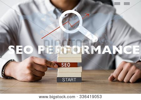 Cropped View Of Seo Manager Holding Rectangle With Seo Lettering And Sitting Near Seo Performance Il
