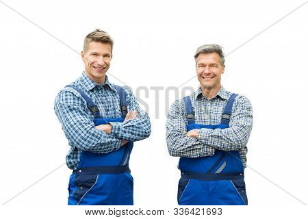 Smiling Portrait Of Two Male Handymen With Arms Crossed Looking At Camera Against White Background