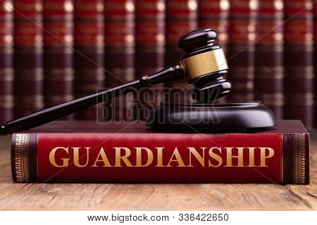 Judge Gavel And Striking Block Over Law Book With Guardianship Law Text On Wooden Desk
