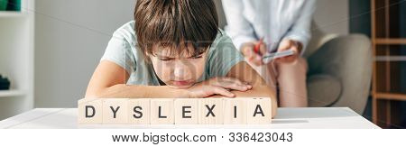 Panoramic Shot Of Sad Kid With Dyslexia Sitting At Table With Wooden Cubes With Lettering Dyslexia