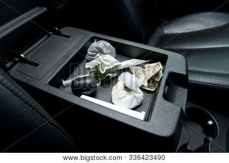 Crumpled Dollars And Various Drugs For Testing Are In The Armrest Of The Drug Dealer S Car, Close Up