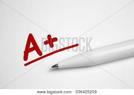 A Plus A Grade Written In Red Pen On Notebook Paper.