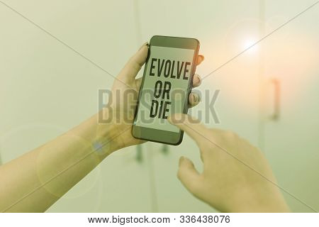 Word writing text Evolve Or Die. Business concept for Necessity of change grow adapt to continue living Survival woman using smartphone office supplies technological devices inside home. poster